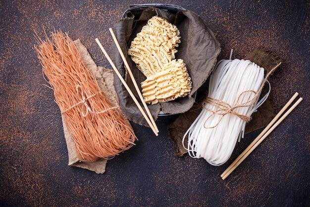 Различные азиатские рисовая лапша на ржавом фоне Premium Фотографии