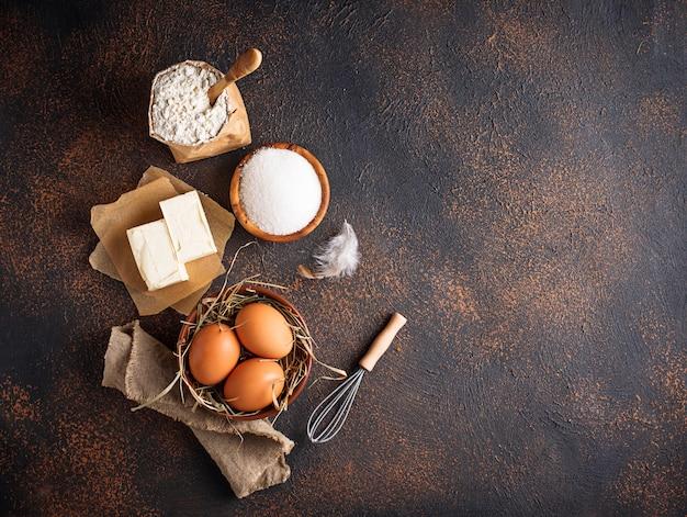 焼くための材料。バター、卵、砂糖、小麦粉 Premium写真
