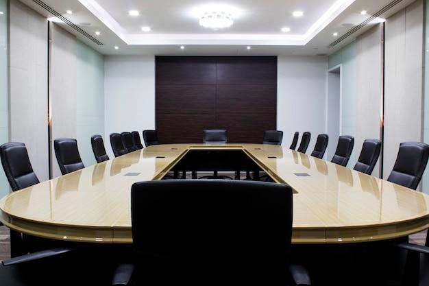 テーブルと椅子のあるモダンな会議室。コンセプト修道院の部屋。会議室 Premium写真