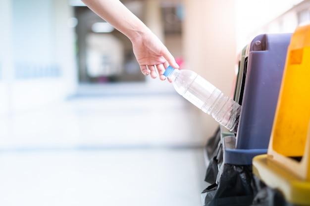 Рука женщины, которая держит бутылку, выбрасывает ее в мусорное ведро. Premium Фотографии