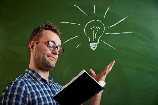 Молодой человек в очках читает книгу, приходит мысль Premium Фотографии