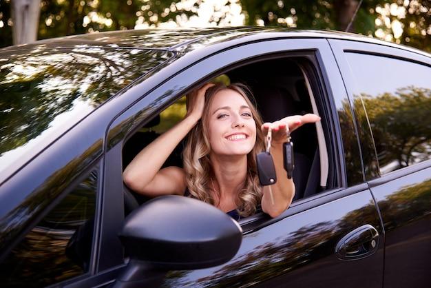 自動でキーを持つ幸せな若い女性。 Premium写真