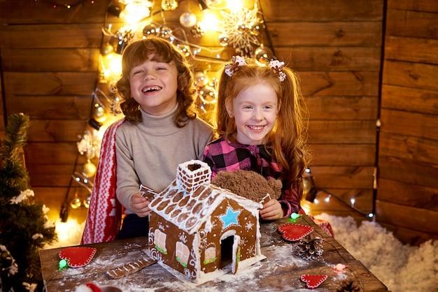 幸せな赤毛のクリスマスジンジャーブレッドとテーブルで少女。 Premium写真