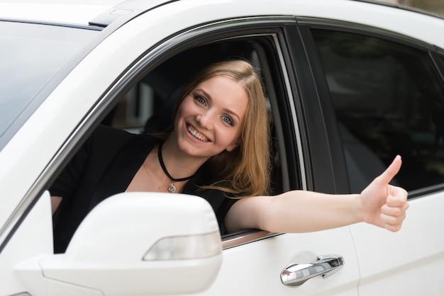 幸せな女の子は車の窓からのぞき見します。 Premium写真
