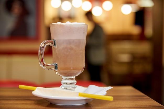ミルクはカフェで木製のテーブルの上のストローで振る。 Premium写真