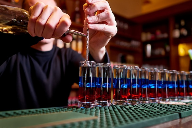 バーカウンターのアルコールショット。プロのバーテンダーがアルコールを注ぎます。 Premium写真