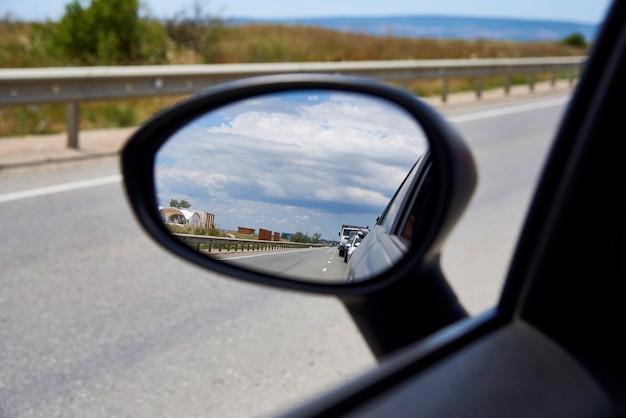 車の鏡の中の空の反射。 Premium写真