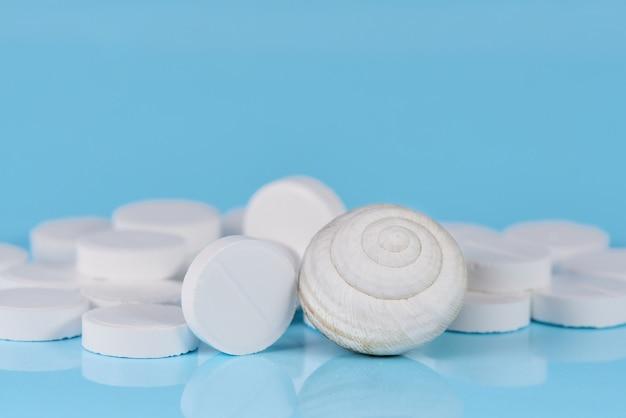 青色の背景にシェルと白い錠剤。 Premium写真