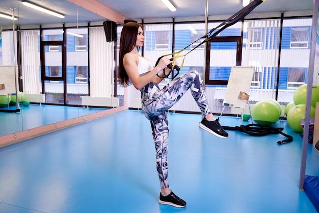 若い女性がジムでフィットネスストラップと運動します。 Premium写真