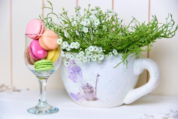 花の美しい装飾的な花瓶の近くのガラスの明るくカラフルなビスケット。 Premium写真