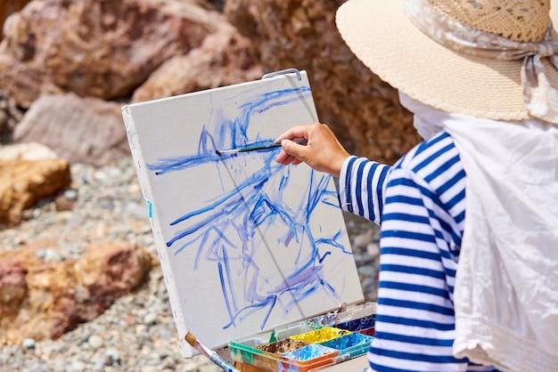 芸術家は海岸に絵を描く。 Premium写真