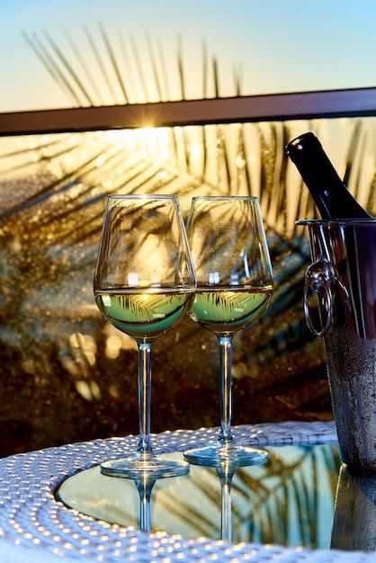 Два бокала белого холодного вина на стеклянном столе на балконе Premium Фотографии