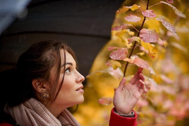 Молодая женщина с зонтиком в осенний парк. Premium Фотографии
