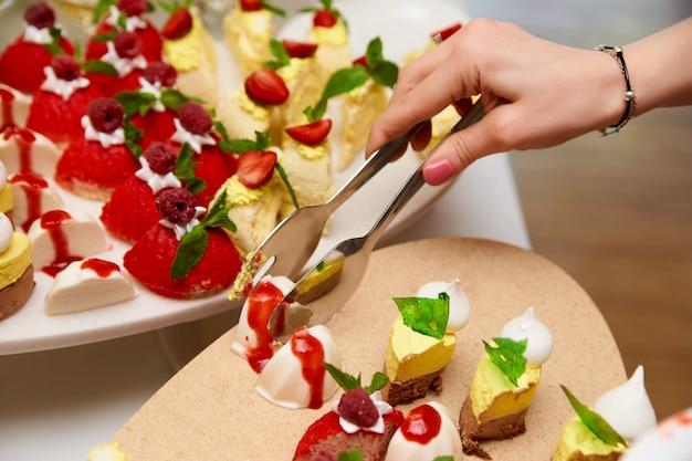 女性の手がビュッフェからケーキを取ります。 Premium写真