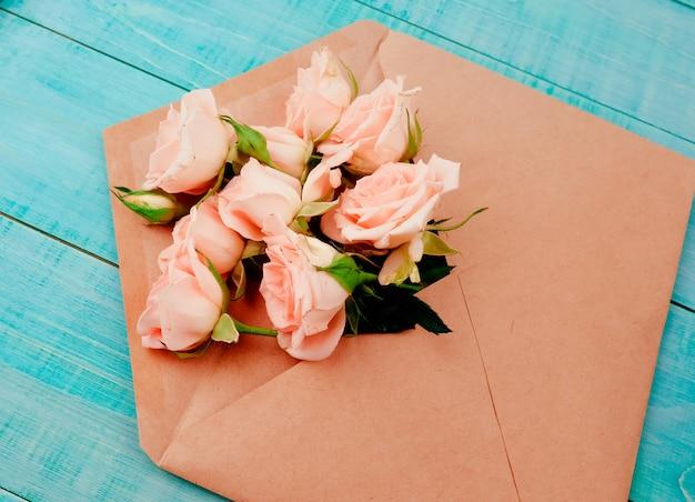 クラフト封筒、コピースペース、青い背景の花 Premium写真