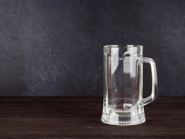 ウッドの背景の空の透明ビールグラス Premium写真