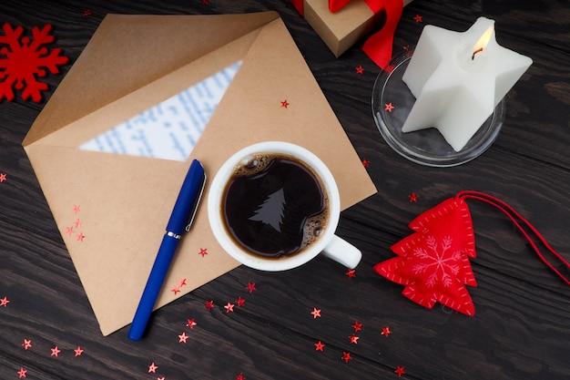 テーブルの上のクリーム色のクリスマスツリーとコーヒーのカップ。サンタクロースへの手紙。 Premium写真