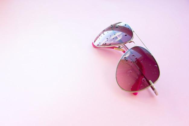 反射、ミニマリスト、コピースペースで、ピンクの背景にピンクのサングラス。 Premium写真