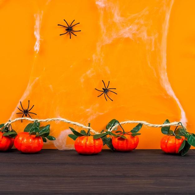 クモの巣の背景、コウモリとクモの巣、ハロウィーンとオレンジ色の背景の前に空の素朴なテーブル Premium写真