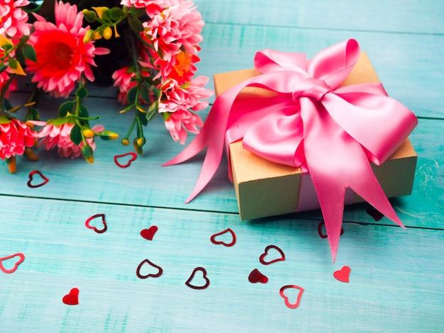 Подарочная коробка с розовой атласной лентой на синем фоне Premium Фотографии