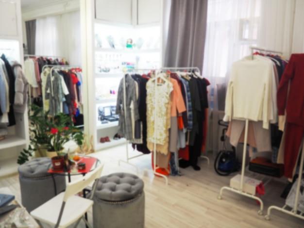 Размытые одежды на вешалке в магазине одежды. абстрактный размытия и расфокусированным торговый центр интерьера универмага Premium Фотографии