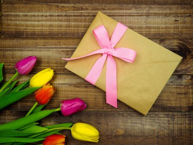 Конверт крафт с розовой лентой на деревянном фоне с тюльпанами Premium Фотографии
