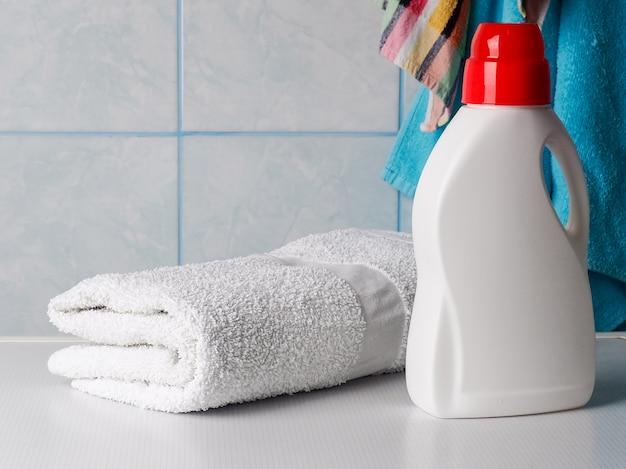 洗剤のボトルと室内の洗濯機の清潔なタオル Premium写真
