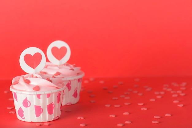 赤の背景においしいピンクパステルバタークリームカップケーキ Premium写真