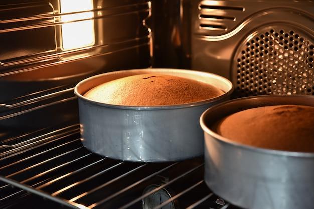 自家製ケーキ、熱いオーブンでチョコレートケーキを焼くのクローズアップ。 Premium写真