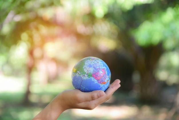 自然の緑の背景を持つ彼女の手に世界のボールを保持している女性。世界環境デーのコンセプトです。 Premium写真