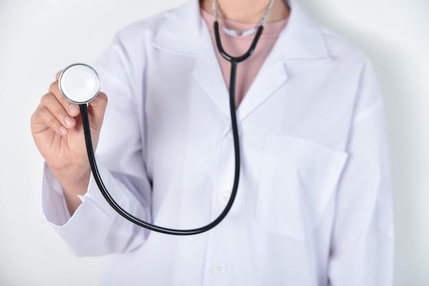 Молодой женский доктор держа стетоскоп в ее руках над белой предпосылкой. Premium Фотографии