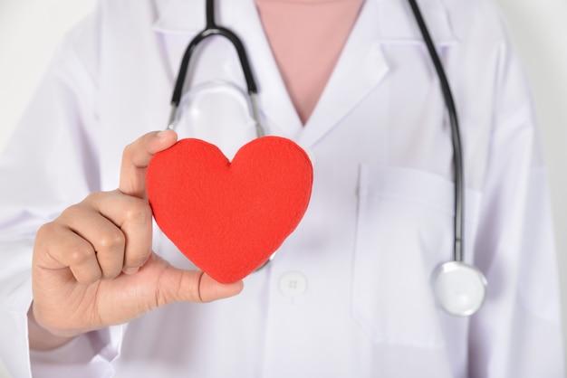 Молодая женщина-врач со стетоскопом держит красное сердце в руке на белом Premium Фотографии