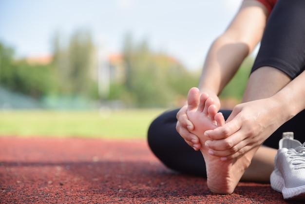実行後に床に彼女の足の痛みをマッサージする女性のクローズアップ。 Premium写真