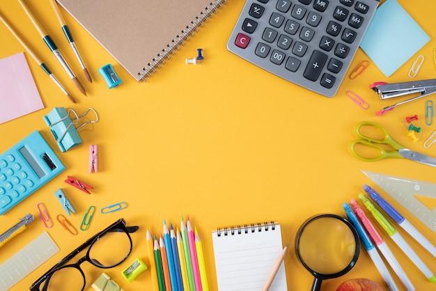 黄色の背景に文房具や学用品のトップビュー Premium写真