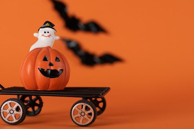 Счастливый хэллоуин праздник фон с тыквой и белым призраком и летучими мышами на оранжевом Premium Фотографии