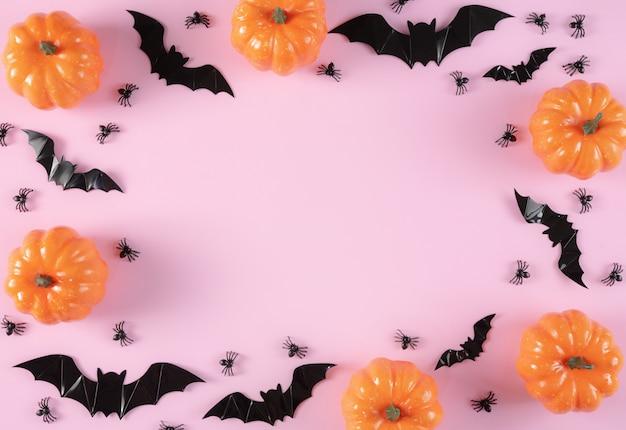 Счастливый хэллоуин праздник фон с кошелек или жизнь, тыквы, конфеты и пауков на фоне пастельных розовых. Premium Фотографии