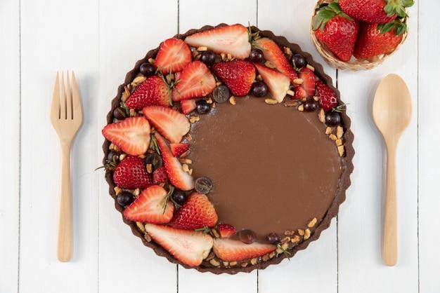 新鮮な果物で飾られたおいしいチョコレート自家製タルト。 Premium写真