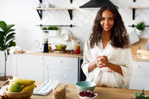 かなりアフリカの女性は牛乳とガラスを保持し、朝食を作るつもりです。 無料写真