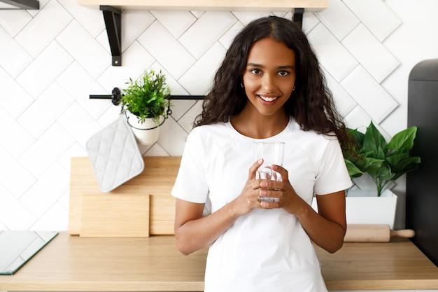 Африканская женщина стоит на кухне и держит стакан с водой Бесплатные Фотографии