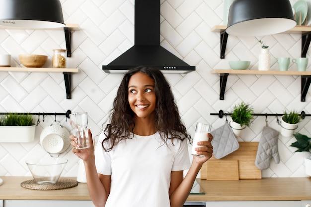 Молодая афро женщина держит два стакана с водой и молоком и думает, какой выбор сделать Бесплатные Фотографии