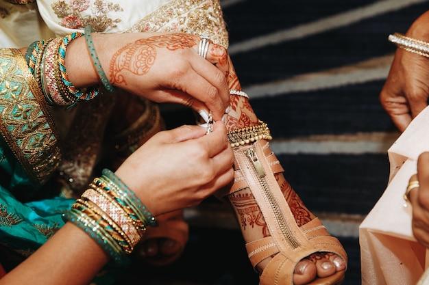 Одевание обуви для индийской невесты перед свадьбой Бесплатные Фотографии