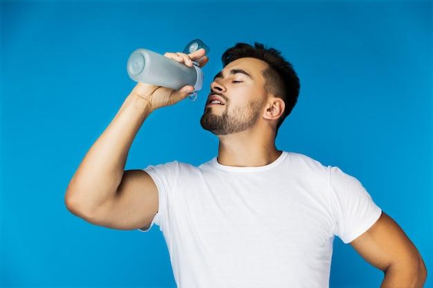 のどが渇いてハンサムな男はスポーツボトルから飲んでいます。 無料写真