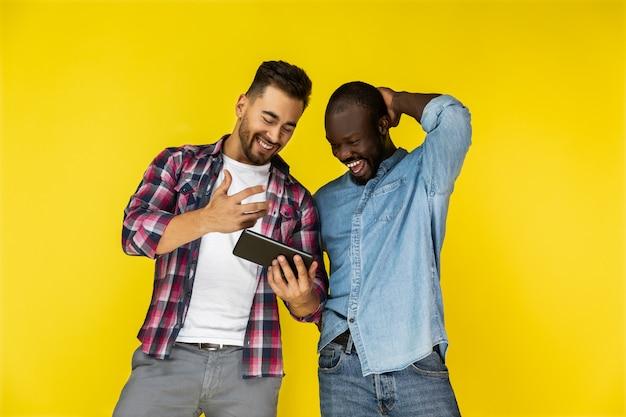 ヨーロッパ人とアフリカ系アメリカ人はタブレットを見て笑っています 無料写真
