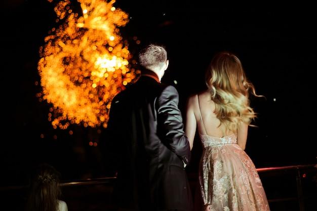 Задняя часть влюбленной пары, которая смотрит фейерверк Бесплатные Фотографии
