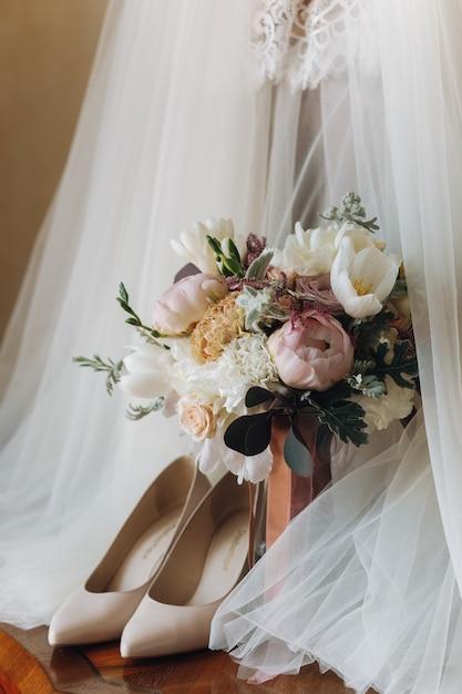 Красивые свадебные туфли, платье и букет цветов Бесплатные Фотографии