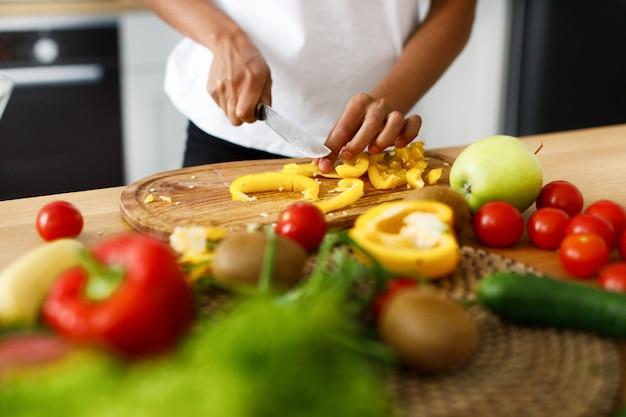 野菜や果物でいっぱいのテーブルで黄ピーマンを切るプロセス 無料写真