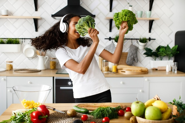 Улыбающаяся женщина-мулатка в больших беспроводных наушниках танцует с листьями салата и брокколи на современной кухне возле стола, полного овощей и фруктов Бесплатные Фотографии