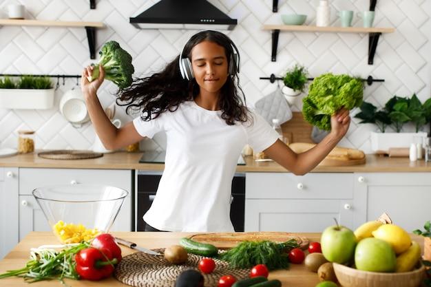 若いアフリカ人女性は目を閉じてヘッドフォンで音楽を聴いて幸せで、ブロッコリーとサラダを保持 無料写真