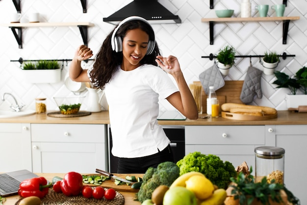 アフリカの若い女性が踊り、台所でヘッドフォンを介して音楽を聴く 無料写真