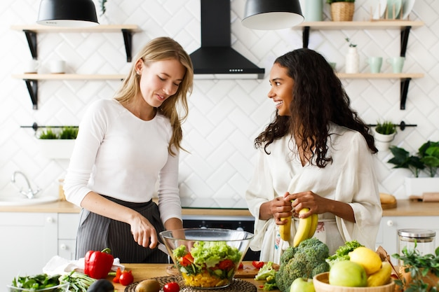 Две привлекательные женщины на кухне готовят здоровый завтрак из фруктов и овощей Бесплатные Фотографии